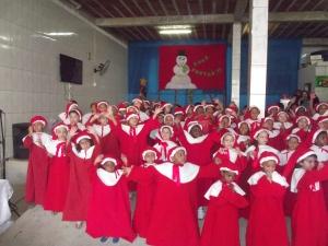Crianças fazem apresentação de natal na chegada do Papai Noel ao Engenho da Serra.