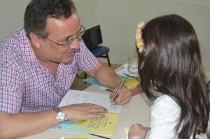 Escritor manhuaçuense, Fabrício Marques, autografa um de seus livros para pequena leitora.