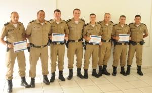 Comandante e subcomandante posam com alguns dos militares agraciados com o certificado de destaque.
