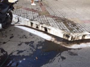 Água suja que saia do esgoto entupido tomou a calçada e a rua.
