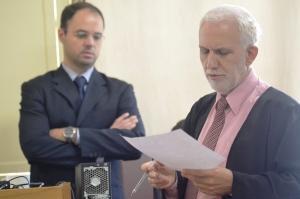 Advogado de defesa, Dr. Roberto Gomes, durante questionamento à réu; juiz observa ao fundo depoimento prestado