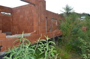 Mato toma conta do terreno; em alguns pontos eles chegam a ultrapassar a construção.