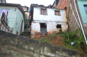 Casa apresenta estrutura bastante danificada, com telhado caindo.